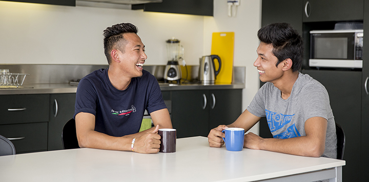 Two students talking in the kitchen